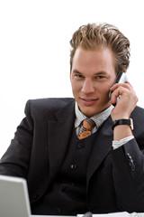 Businessman using laptop computer, mobile phone,