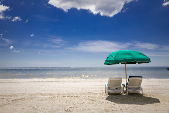sunny beach with green umbrella