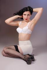 Retro pin-up girl in vintage bra, girdle & fishnet stockings