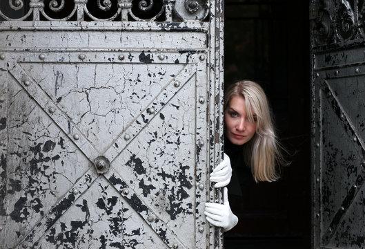 Beautiful woman looking looking out of dark vintage gate