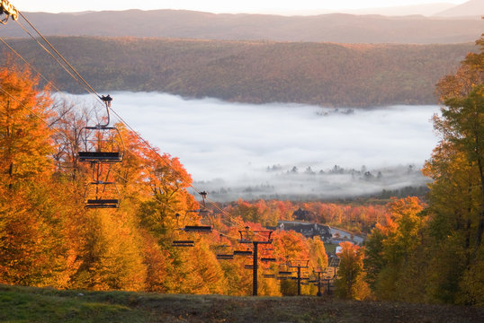 Chairlift on a fall mountain slope with morning mist