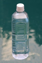 Bottle of pure mineral water  on blue water background