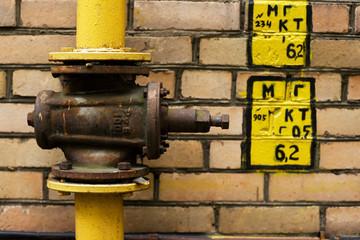 A closeup of a gas valve on a brick wall