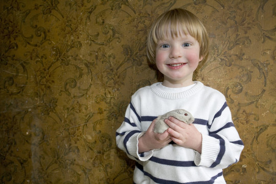 3 and half year old boy holding a pet Gerbill