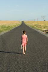 Young gir l walking down a road.