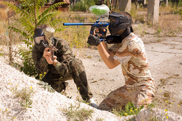 Paintball players hunting outdoors over nature background