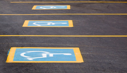 Row of parking spaces with a handicapped sign