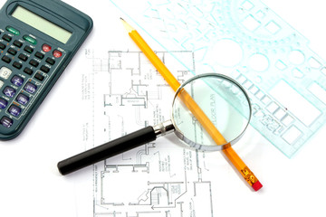 Small magnifier, calculator and pencil on the flat plan