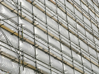 Close up of a high rise building covered in white tarpaulin.