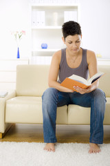 Young woman reading book at home, sitting on sofa.
