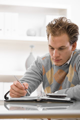 Young man working at home, writing on desk.