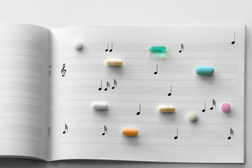 Prescription pills on white lined music note paper
