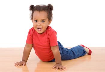 Adorable african baby lying over wooden floor