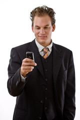 Businessman writing text message on mobile phone,