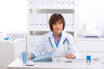 Senior female doctor sitting at desk working at offiice.