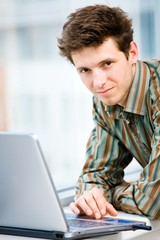 Casual looking happy businessman working on laptop