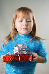 Young girl with unpleasant gift over grey background