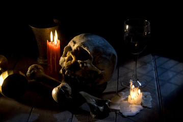 real skull and bones over a table, with candles and chalice.