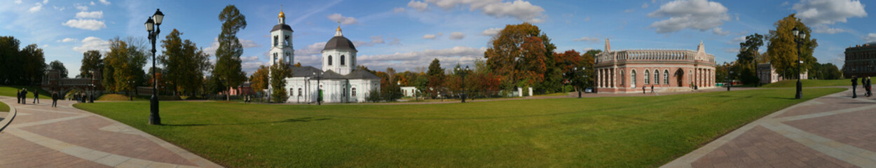 panorama of old church in autumn park at sunny day