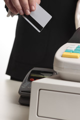A man hands his credit or debit card at checkout for payment.