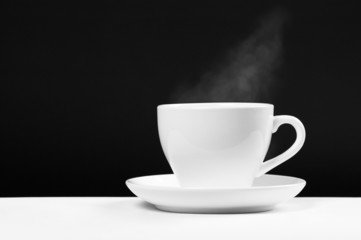 white cup with hot beverage over black background