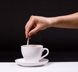 woman stir sugar in cup of coffee over black background