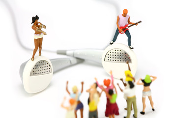 Miniature band standing on a pair of ear buds. MP3 concept.
