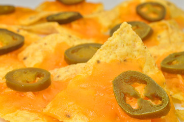 Focus on one nacho on plate of nachos.