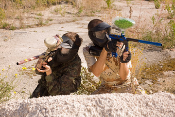 Two paintball players hunting outdoors over nature background