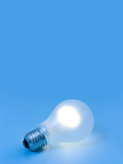 Lighting lamp on blue paper, abstract technology background