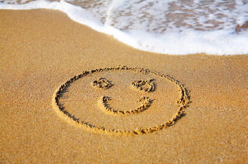 """Smile"" drawing at sand, with sea wave"
