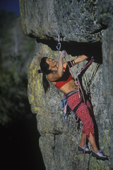 Climber clipping her protection on a crack climb.