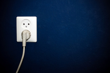 White socket with one old plug in dark blue wall