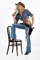 Young blonde woman in cowboy clothes with guns