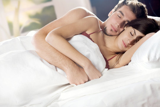 Young couple sleeping and hugging on the bed in bedroom