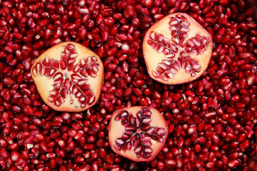 Three halved pomegranates in a bowl of seeds.