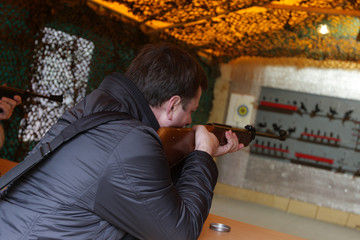 The man shoots in a shooting gallery