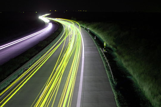 road with car traffic at night and blurry lights showing speed