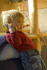 A picture of a boy plaing with a cellphone