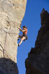Female climber ascending a steep rock face.
