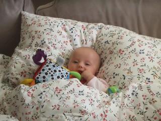 Baby caucasian girl sleeping in parent's bed.