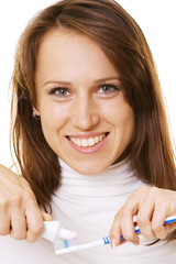 smiley woman with toothpaste and toothbrush over white