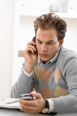 Young man calling on mobile phone at home.