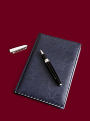 Notebook and pen on a red background