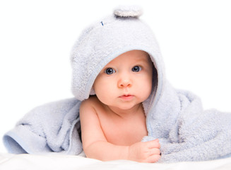 Cute baby girl with towel after bath. Studio shot. Isolated