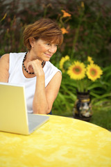 Modern senior woman sitting in the garden at home