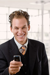 Portrait of happy young businessman smiling at office.