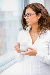 Young businesswoman standing in front of office window,