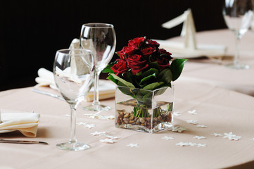 dark red rose arrangement on dinner table