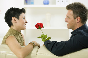 Romantic man giving red rose to woman at home, smiling.